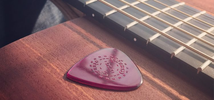An arty shot of the top of a guitar, with a pick on, ready to be played at a live gig.
